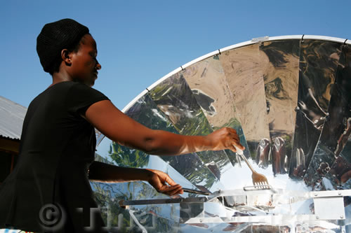 Sophia Ngwira fries tomatoes and onions on a solar cooker outside her house.