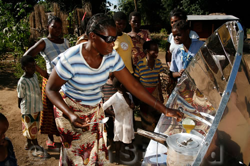 A woman in Fwalu village cooks an omelette on the first solar cooker to be given to the village